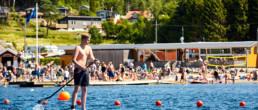 En man på en SUP-bräda paddlar i vattnet en solig dag på västkusten i Bohuslän utanför Strömstad.