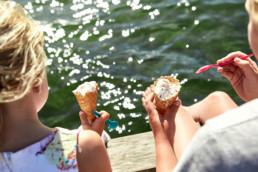 Två barn äter glass på bryggan.