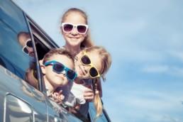 Tre barn med solglasögon sticker ut sina huvuden ur bilfönstret.