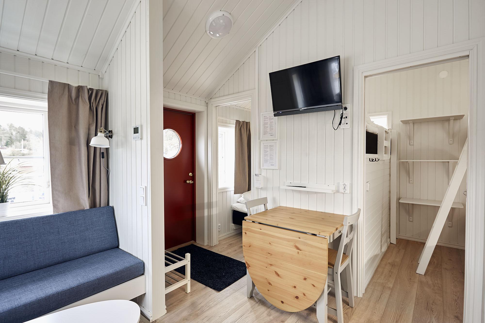 Insidan av ett rum med tv och soffa på Lagunen.