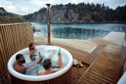 Tre män badar badtunna bara några meter ifrån havsvattnet.