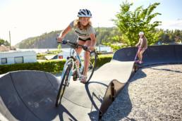 En ung cyklist i Lagunens bikepark utanför Strömstad. I bakgrunden åker en person kick-bike.