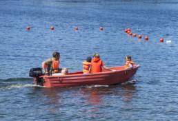 Fyra personer i flytvästar sittandes i en motorbåt.