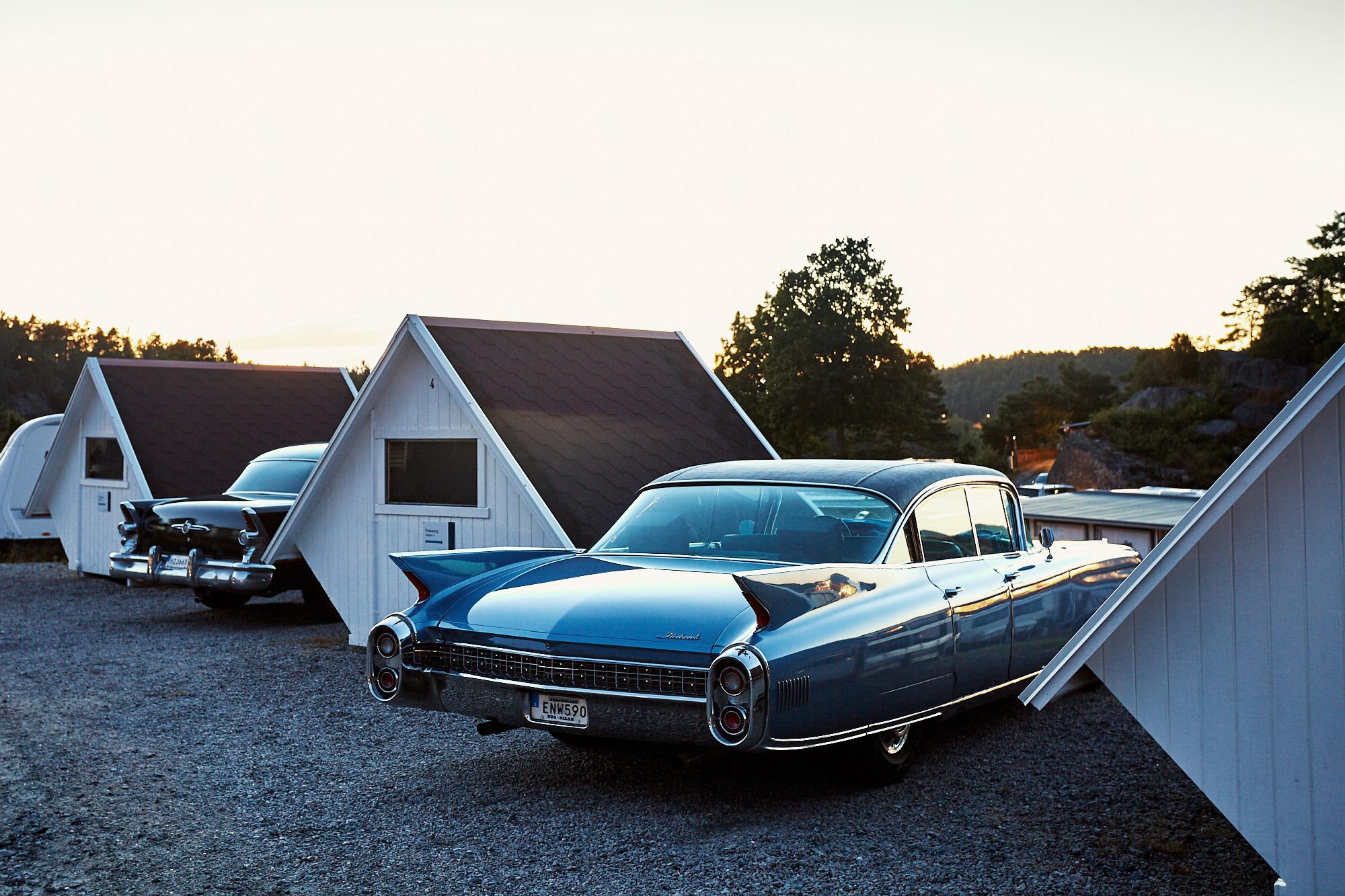 Två äldre amerikanska bilar parkerade på Lagunen med den bohuslänska solen som går ner i bakgrunden.