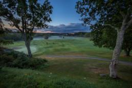 Bild på en golfbana med gröna gräsmattor, när solen nästan helt är nere.