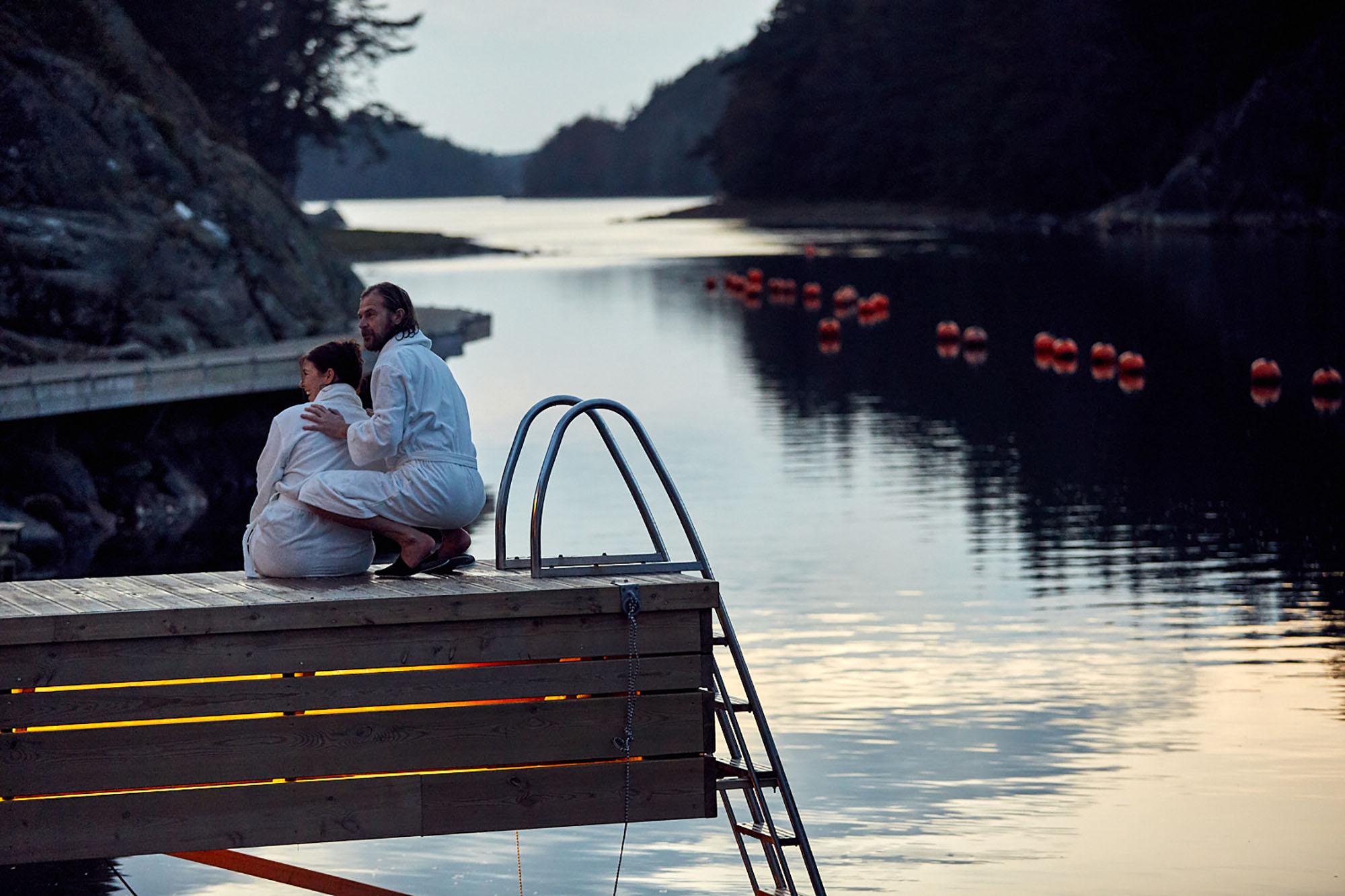 Två personer ute på bryggan nära vattnet. De är iklädda badrockar.