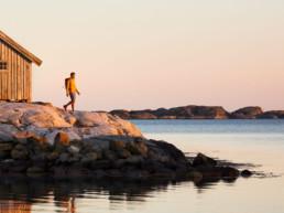 Man på klippor i den bohuslänska skärgården på västkusten i solnedgång.