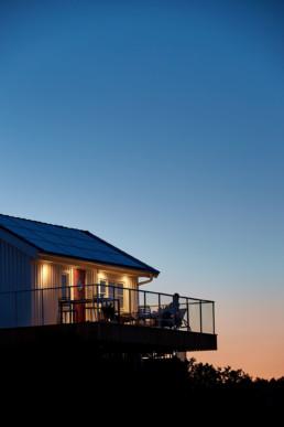 Stuga i solnedgång med personer på balkongen.
