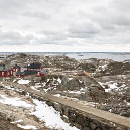 Bild på Ursholmens stugor på västkusten med snö på klipporna.