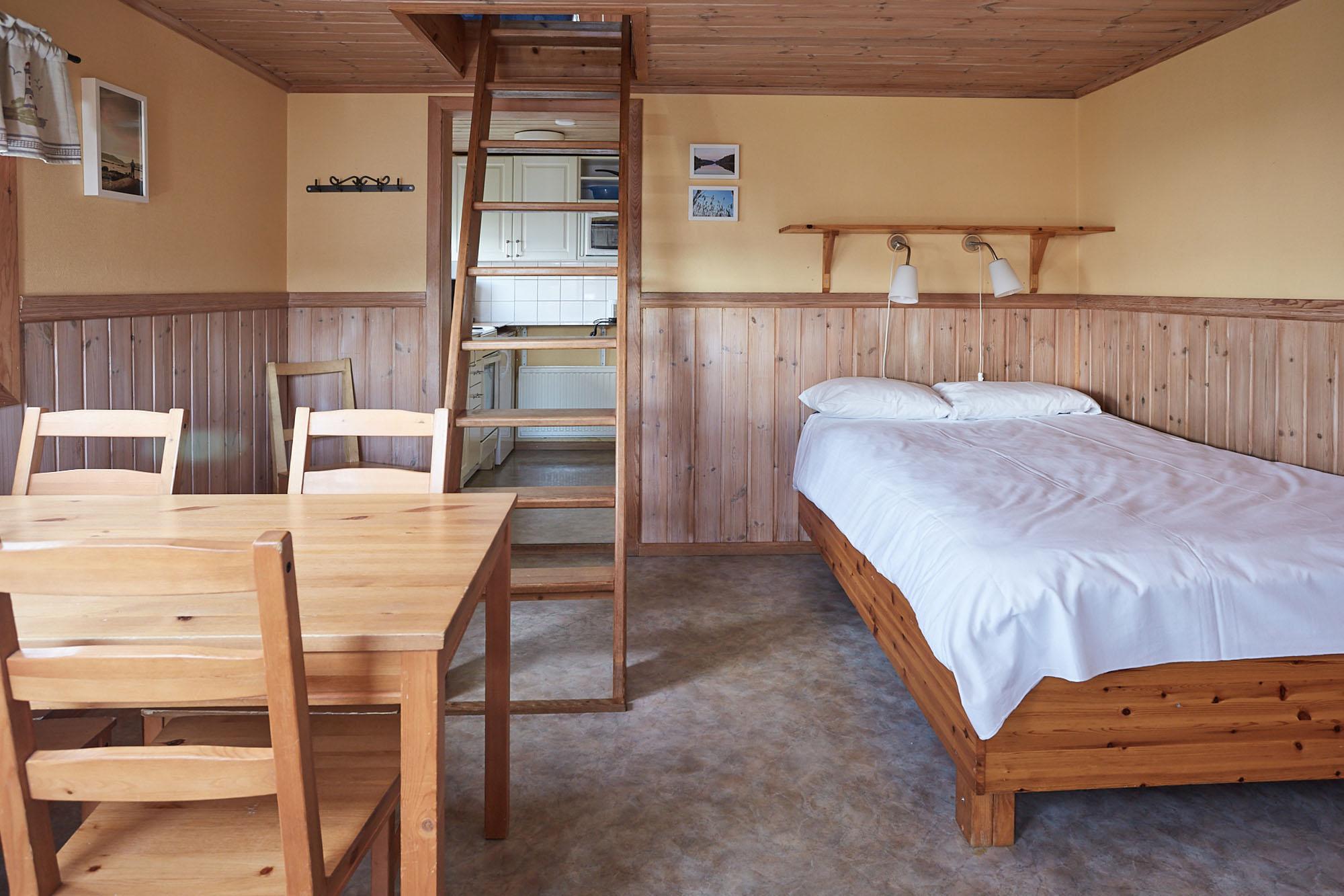 Insidan av Ekebostugan med säng och bord.
