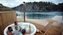 Tre personer dricker öl och umgås i en badtunna precis intill vattnet på Lagunen i Bohuslän.